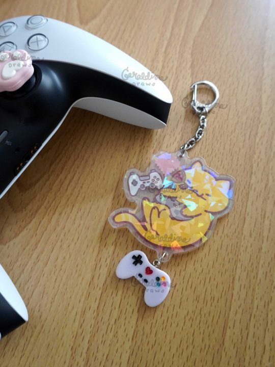 gamer kitty keychain with lavender charm next to a ps5 controller